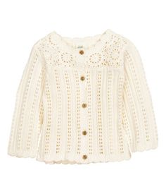 Pattern-knit cardigan in soft cotton. Crocheted section at top, buttons at front, and decorative scalloped trim.