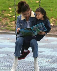 Selena Gomez reading to a fan at the park.