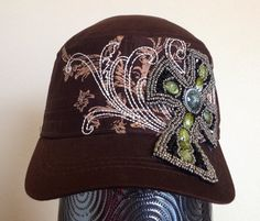 This brown cadet cap features a beige screen printed pattern across the front of the hat, along with white embroidery that follows the pattern. There is a black fabric cross embellished with metallic and green patterned beading that covers part of the front and bill of the cap.  - Three-panel construction. - Embroidered design. - Screen printed design. - Patterned and metallic beads. - Adjustable closure at back. - 100% Cotton.