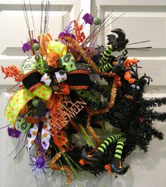 Sparkle this Halloween with a fun wreath full of spooky bats, pumpkins, spiders and webs. Built on a round black grapevine base, there are two sets of witch legs, a large black spider, pumpkin picks,