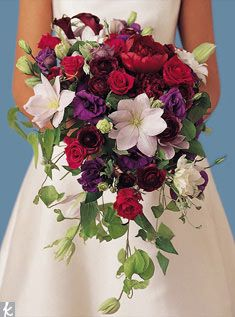 purple lisianthus, deep burgundy peonies, dark purple calla lilies, red roses, and lavender passion flower cascade wedding bouquet