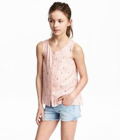 Light pink/ice cream. Sleeveless, flared top in woven fabric with a printed pattern. Chest pocket, buttons at front, and gathered yoke at back.