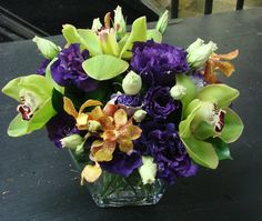 This is a floral arrangement that features cymbidium orchids, mokara orchids and lisianthus in a purple, green and orange color scheme.  See our entire selection at www.starflor.com.  To purchase any of our floral selections, as gifts or décor, please call us at 800.520.8999 or visit our e-commerce portal at www.Starbrightnyc.com. This composition of flowers is generally available for same day delivery in New York City (NYC).  LV038