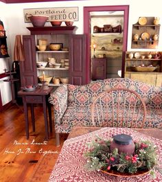 The organization looks like a store, not a home, but I love the items shown, especially the idea of a print couch with primitive solid-colored cabinets.