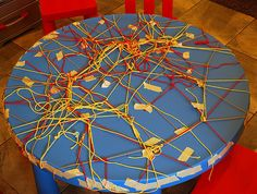 tape a piece of thread to side of table and children thread wherever they wish to the other side...