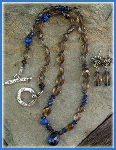 """Midnight Blues -Smokey Quartz faceted ovals -AAA Lapis Lazuli faceted rondelles -Kyanite faceted rondelles 3 & 4 mm -Kyanite Faceted Briolette Pendant 9 x 12mm -Artisan Crafted Silver Toggle by """"Stephanie Olin""""  inscribed """"Hope*Faith*Love on backside -Hand-Knotted on Jeweler's Silk  -Necklace measures......16.5 inches -Earrings are Silver Post-Style w/ a one inch dangle"""