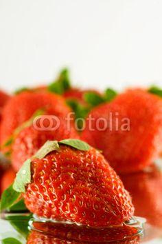 Strawberry falling in juice