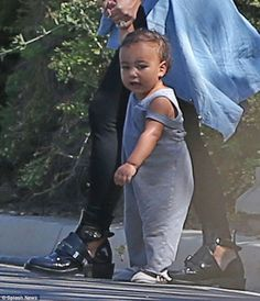Early walker: North is on her feet at just 13 months of age, albeit holding on tight to Kim's hand