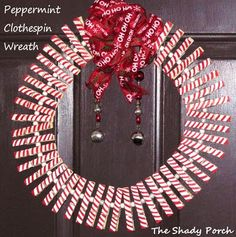 Peppermint Clothespin Wreath - simply a clothes hanger some clothespins painted white then striped with a red marker. Add a bow and bells and it's done! #wreath #peppermint #clothespin