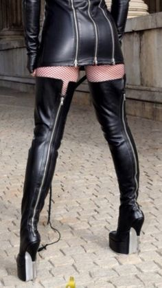 Long sleeve leather minidress and thigh boots fetish wear