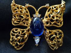 SIGNED CARNEGIE GOLDTONE BUTTERFLY WITH BLUE CABACHON & RHINESTONE BODY