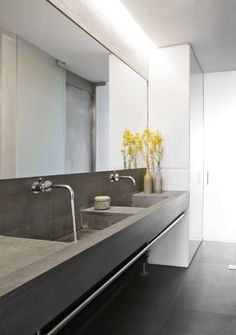 12 Concrete Interiors: Solenne de La Fouchardiere, one of the principals of UK-based design firm Ochre, designed her own East London loft with plenty of concrete. The double trough-style sink is super spacious, and one could hang a hundred towels on the bar underneath the entire expanse.