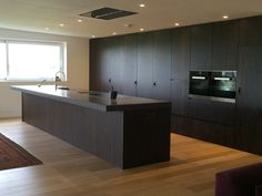 Solid wood kitchen with concrete worktop, eye-level ovens, integrated appliances, stainless steel sinks and induction hob