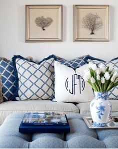 Blue & white pillow with monogram- tufted ottoman and flowers in a ginger jar. Love those pictures on the wall too.