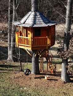 A neat tree house with eight sides and a tire swing