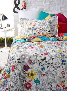 Desigual at Simons Maison.  A reversible design with an ultra funky, multicolored mosaic on one side and pop-coloured accents on the other amid a bevy of drawings, hand-sketched in black felt against a white background.  Matching pillow sham sold separately.      Dimensions:   Queen: 240 x 220 cm    *Home decor shown is for illustrative purposes only.