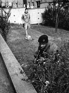 """Philip Jones Griffith: Mowing the lawn, Northern Ireland, 1973 : """"The incongruities of daily life in the urban war zone. For years, the people of Northern Ireland lived in a strange and strained symbiosis with the occupying British army. British Soldier, British Army, Belfast, Bobby Sands, Northern Ireland Troubles, Old Photography, Photographer Portfolio, Magnum Photos, Military History"""