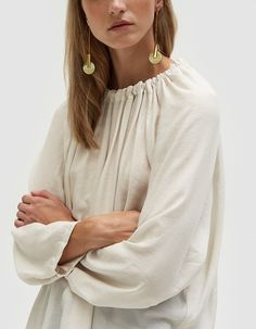 Contemporary top from NEED in Ivory. Luxe fabrication. Adjustable neckline with grosgrain closure. Long raglan sleeves. Delicate snap detail at cuff allows for pleating. Shirttail hem. Oversize fit.