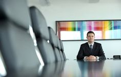 What I think stands out within this image is the main focal point is the businessman, sitting at the head of the table, where all the empty seats of what looks like a meeting room are out of focus, giving the full attention on him but he's composed so he's not at the centre of the image and that it's not a plain, normal focused image. The businessman is also sitting under the most colourful eye catching part of the image.