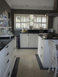Heel mooie landelijke keuken met zwart aanrechtblad en witte shutters