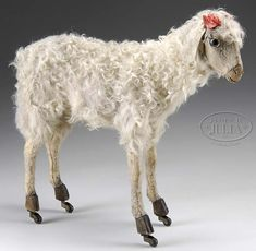 """*SHEEP ON WHEELS PULL TOY ~ Attractive pull toy made of papier mache covered in white fleece w/hide muzzle, glass eyes + white kid ears. SIZE: 15"""" t. x 17""""."""