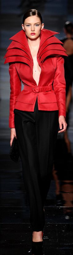 Like the style of the red jacket open and belted over the elegant black shimmer pant.