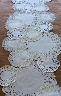 You can make a table runner using multiple sizes and shapes of paper doilies. | via Love That Party