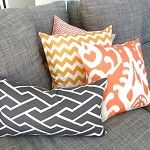 Lovely tangerine ikat and chevron cushions, combined well with dark grey geometrics and the grey lounge.