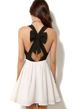 Une robe à moitié blanche, moitié noire. Le premierière moitié est noire avec un nœud sur le dos de la robe. Le dos a un quadrillage en losanges aussie. Le deuxième moitié est une jupe plissée.
