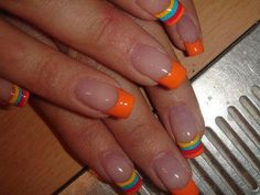 Nude nails with bright orange french tips and a single multi-color (orange, turquoise or teal, yellow) striped accent nail on each hand. Easy, free-hand, nail art