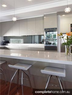 White gloss cabinetry and grey benchtops for the kitchen (opposite way round to this) with the Mirrored splashback