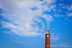 Tall lighthouse tower with clock on top in daytime. blue sky, white cloud