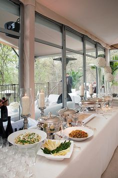 Among all white decor, pasta dishes sit brightly next to bottles of red wine for a Middle Eastern wedding celebration.