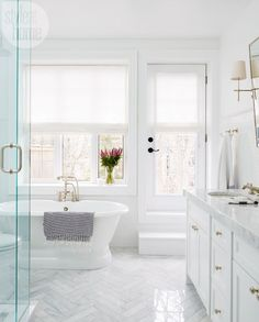 herringbone marble tile floors with marble counters. Shaker style cabinets with deep soaker tub. dream bath, white and gray with gold touches round out this beautiful master bath