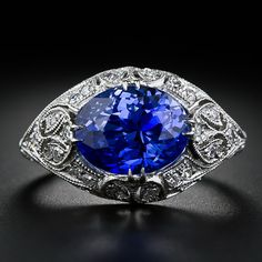 A bright and sizzling electric blue sapphire of Ceylon origin, weighing 5.44 carats, scintillates horizontally from an exquisitely detailed, hand-crafted platinum and diamond mounting, circa 1900. Delicately applied open-work ornamentation with fine milgrain work combines with a geometric zig-zag gallery for a romantic and ravishing effect.