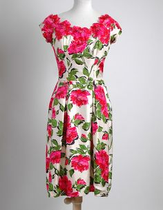 Pretty 1950's floral silk cocktail dress with appliqued flowers around the neckline. Fabric is a fine silk with a subtle faille weave, bright cerise and red flowers. Two little bows at the waist and one in the back. Box-pleated skirt. Metal zipper up the back. Union label. Fully lined.