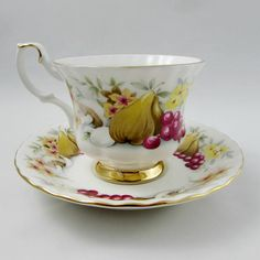 Beautiful vintage bone china tea cup and saucer made by Royal Albert. Pattern is Devon in the Country Fayre Series. Tea cup and saucer have a floral and fruit pattern. Gold trimming on cup and saucer edges. Excellent condition (see photos). The markings read: Royal Albert Bone China
