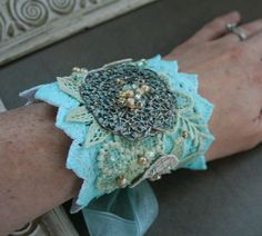 From the Gilded Dragonfly -BY THE SEA- ooak tattered lace cuff bracelet with hand sewn embellishments. $50.00, via Etsy.