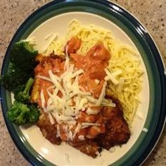 Homemade Chicken Parmigiana Recipe: Melted Parmesan and mozzarella cheese, and a peppery, garlicky tomato sauce drizzled over the top of a chicken fillet.