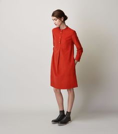 Collarless, A-line shirt dress in a soft, light needlecord. Four-button opening, with pleat below. Two patch pockets. Two slip-in pockets. Bracelet length sleeves and double buttoned cuff. Box pleat into back yoke.