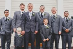 Formal groomsmen outfit idea - dark gray suits with black bow ties and matching boutonnieres {Woodland Fields Photography}