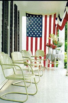 Ready for sparklers! Besides loving the big American flag and the bunting, I also like the white, glossy-painted floor of this porch and the vintage  metal lawn chairs. (July 4th, bunting, U.S. flag)