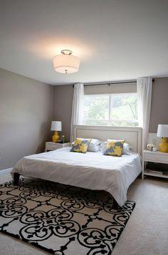 schlafzimmer design wandfarbe grautöne bett teppich gelbe akzente