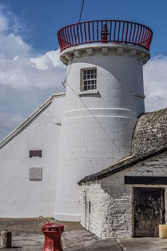 Lighthouse, built 1761, of tapered profile on a circular plan. Cast-iron railed walkway supported by console surrounding lantern. Accessed through adjoining single-bay single-storey building with steps up to entrance level.
