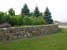 Curved stone wall, dry (no concrete) construction.