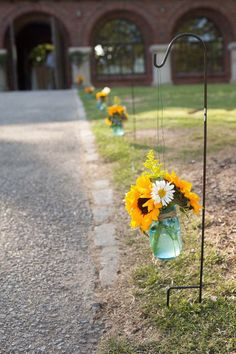 The sidewalk at Avondale Villa was lined with blue mason jars on shepherd hooks filled with sunflowers, daisies, and solidago.