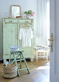 Beautiful soft green paint color on armoire. Hang attire outside. Notice the blue door entrance.