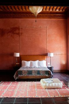 A hotel El  Fenn in Marrakech; Morocco. This is a beautiful bedroom with burnt sienna walls and oriental carpets. Sometimes less is more, would love to stay here.