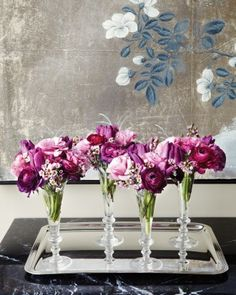 This arrangement features purple tulips, lisianthus, waxflowers, and ranunculus in similar shades. Four individual arrangements are nestled in Champagne flutes, a great unique vessel for flowers.