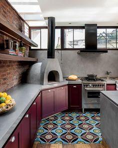 Ladrilhos hidráulicos e armários laqueados colorem a cozinha gourmet. A bancada de Quartzo Stone com forno de pizza embala o preparo das delícias. Projeto @fedabbur_arquitetura 📷 Adriano Escanhuela #revistaaec #arquitetura